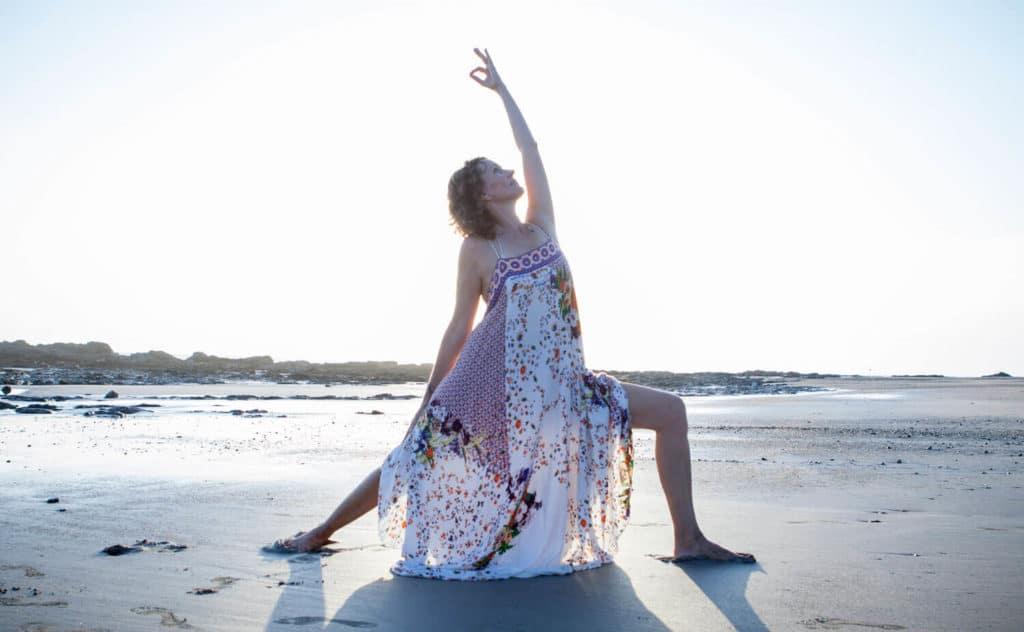 Dagmar doing warrior II pose on the beach